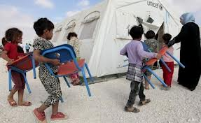 Students carry their chairs into a UNICEF run school in Zaatari Camp near Irbid, Jordan. Photo credit: http://english.alarabiya.net/articles/2013/02/03/264213.html